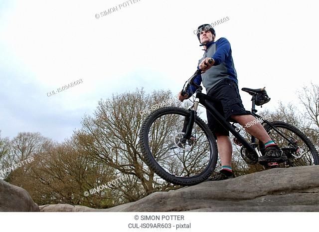 Mature male mountain biker looking out from rock formation