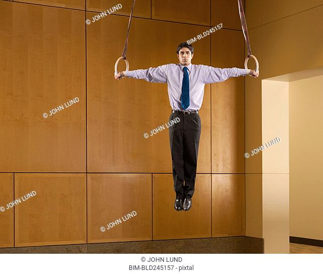 Hispanic businessman using on gymnastic rings