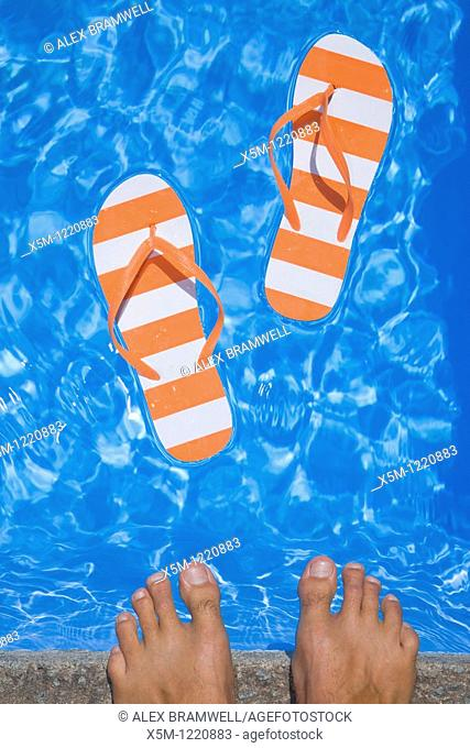 Pretty pair of stripey flip flops or thongs in a sparkling blue swimming pool with a man's feet