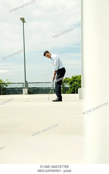 Business man golfing on parking level