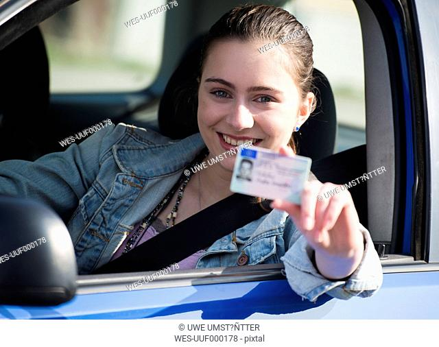 Smiling teenage girl sitting in car showing driving license, partial view
