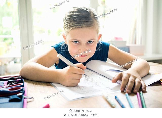Portrait of girl doing homework at table