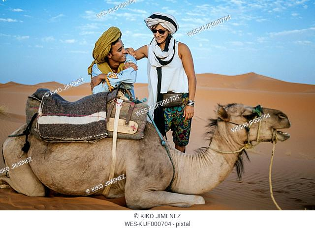 Berber man with woman tourist with a camel in the desert