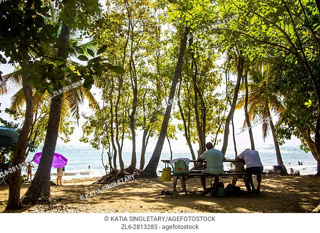 People sitting down at a picnic table with the ocean front of, at the beach Les Salines in Martinique
