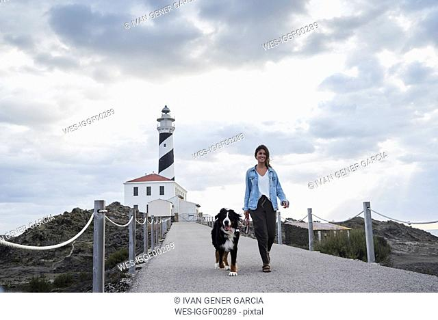 Spain, Menorca, Bernese mountain dog walking together with his owner outdoors at lighthouse