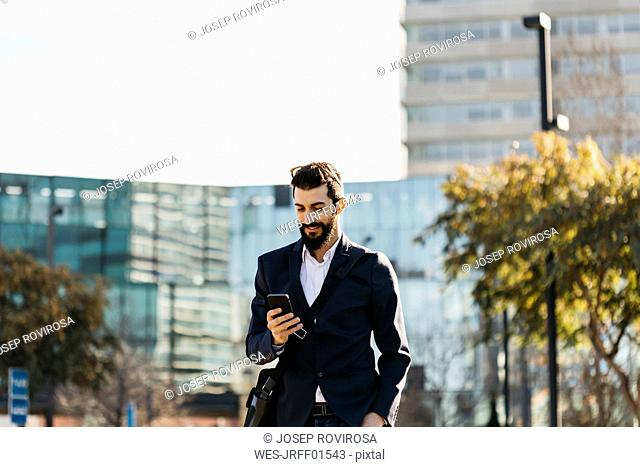 Businessman using cell phone outside office building