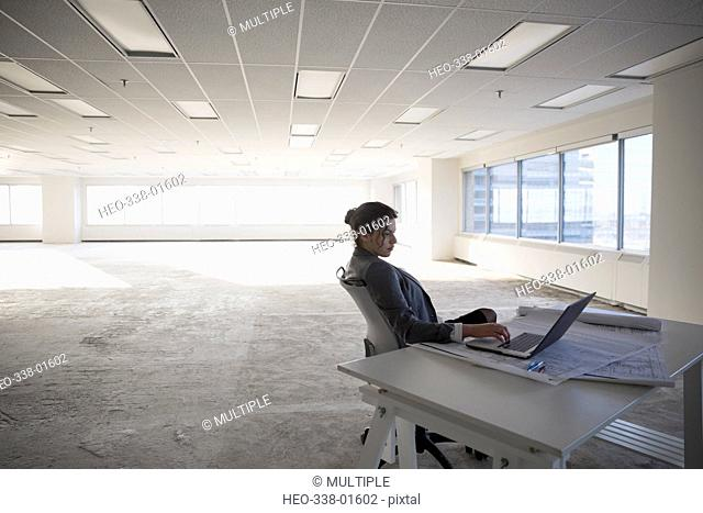 Female architect working at laptop in empty, unfinished open plan office