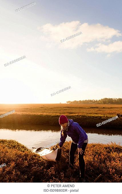 Mid adult woman pulling kayak onto riverbank at sunset, Morro Bay, California, USA