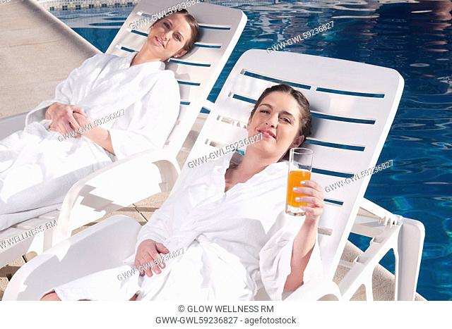 Two women resting on lounge chairs at poolside