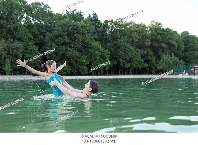 Grandmother enjoying with granddaughter in swimming pool against trees