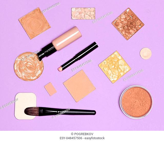Makeup cosmetics for the perfect complexion, flat lay set. Concealer pencil, foundation fluid with bronzing, highlighting, shimmer golden powder