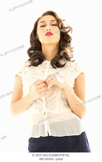 Beautiful young woman in white blouse and blue denim skirt, with head tilted back showing authority, confidence or defiance