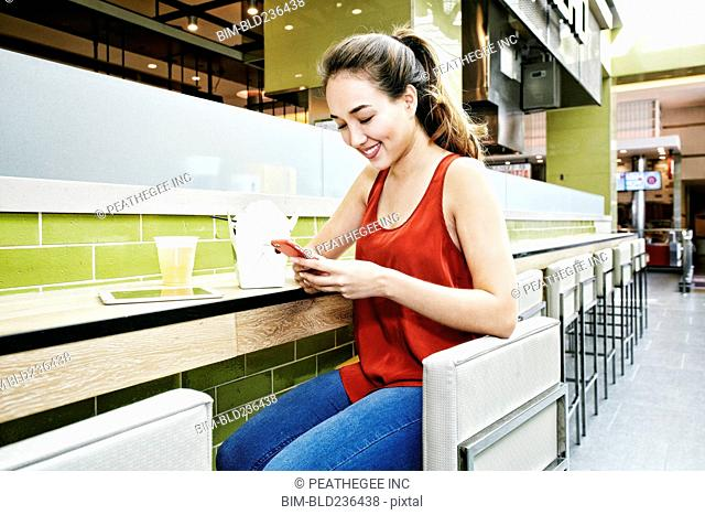 Mixed Race woman in food court texting on cell phone