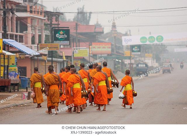 Buddhistic monks walking on a street and collecting alms at sunrise, Vang vieng, North Laos, Laos
