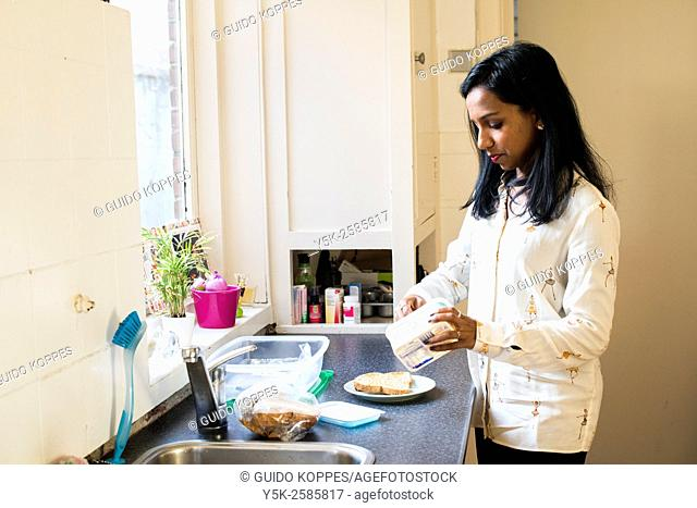 Tilburg, Netherlands. Young, dark skinned woman doing the dishes after lunch at home