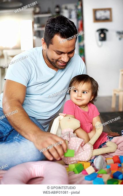 Smiling father and baby girl playing with building blocks at home