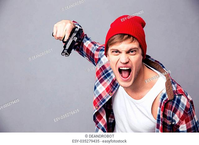 Dangerous agressive young man in checkered shirt and red hat
