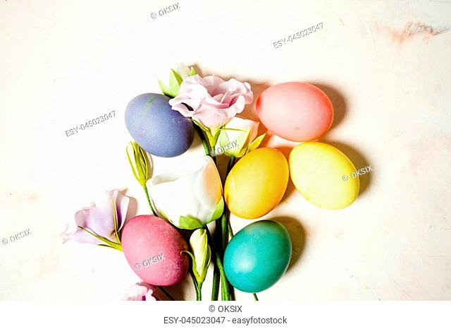 Flowers and eggs on pink mable background, copy space for Easter greetings