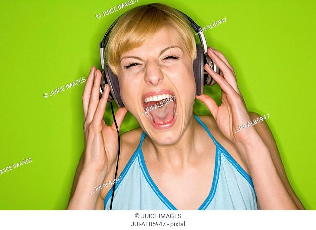 Woman wearing headphones and yelling
