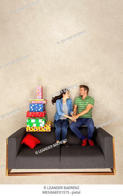 Happy couple sitting on couch with pile of presents