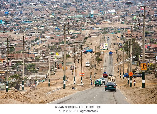 A sprawling settlement of houses, cut by a single road, is seen on the dusty hillsides of Pachacútec, a desert suburb of Lima, Peru, 24 January 2015