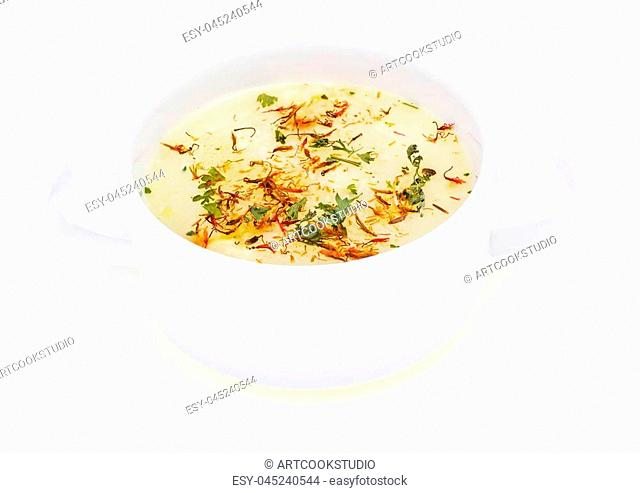 Vegetable soup with saffron in white bowl. Studio Photo