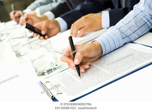 Image of human hand over paper during business seminar