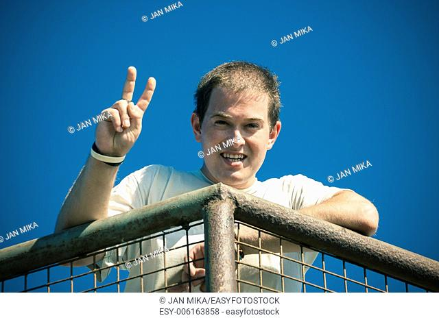 Young happy man gesturing v sign