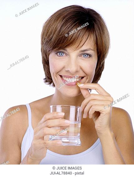 Studio shot of woman about to take vitamin