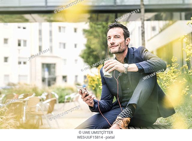 Businessman sitting outside, taking a break, listening music from his smartphone, drinking coffee