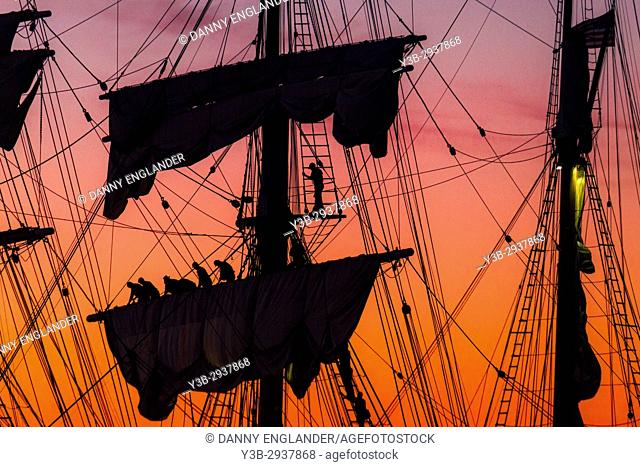 Sailors rolling up sails at sunset on the Star of India sailing ship in San Diego, CA