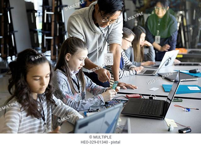 Male teacher helping pre-adolescent girl assembling and programming electronics in classroom