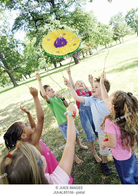 Group of young children playing with pinata outdoors