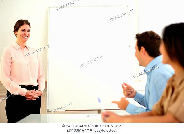 Portrait of pretty caucasian busisesswoman smiling and looking at professional group on office meeting - copyspace