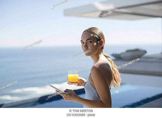 Portrait woman using digital tablet and drinking orange juice on sunny luxury patio with ocean view