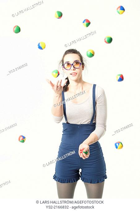 Concentrated young hispanic woman with glasses juggling with many balls