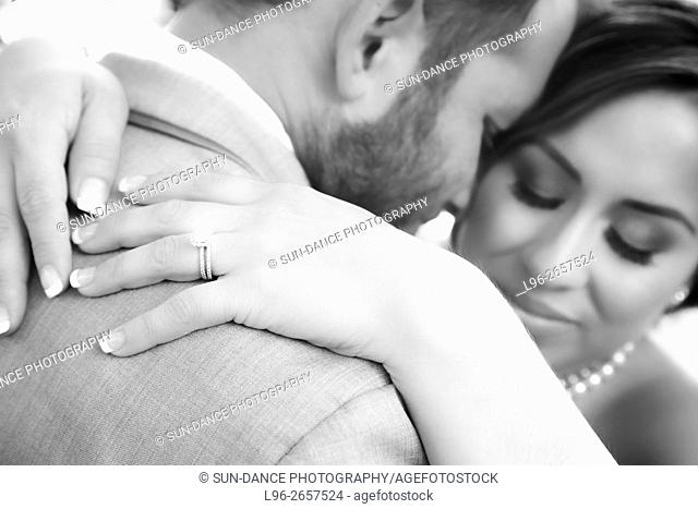 b&w close up of wedding ring bride & groom embrace