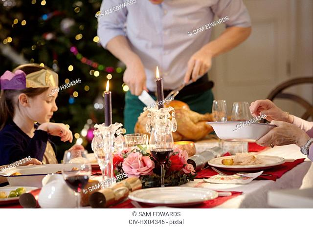 Father carving Christmas turkey at candlelight dinner table