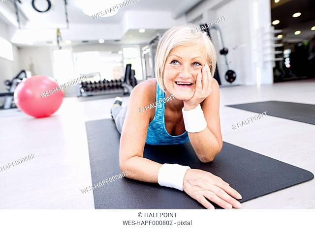 Smiling mature woman lying on gym mat in fitness gym