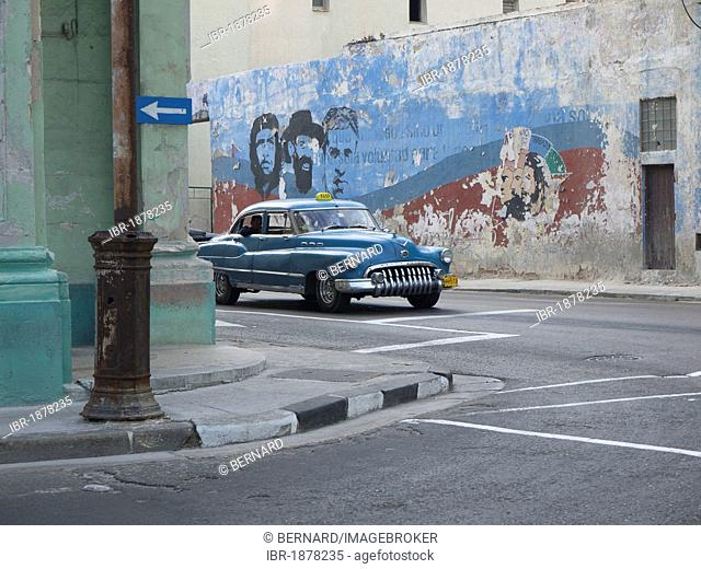 American vintage car driving along a wall with paintings of Fidel Castro and Che Guevara, Havana, Cuba, Latin America