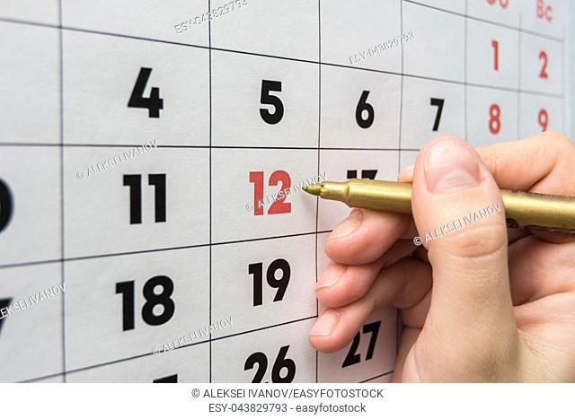 Hand marker indicates the 12th number in the wall calendar