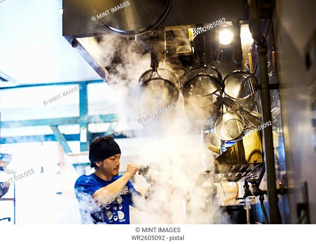 The ramen noodle shop. A chef working in a kitchen with steam rising from the pots of noodles