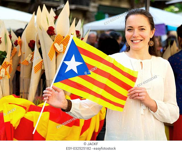 Happy woman with Flag of Catalonia during Sant Jordi festival in Barcelona, Spain