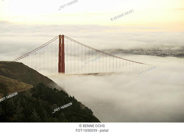 Golden Gate Bridge surrounded by fog over San Francisco Bay during sunset, California, USA