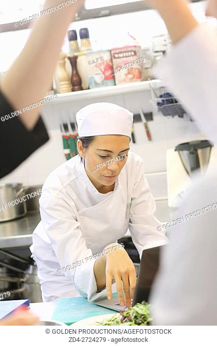 Pensive chef in restaurant kitchen with laptop computer