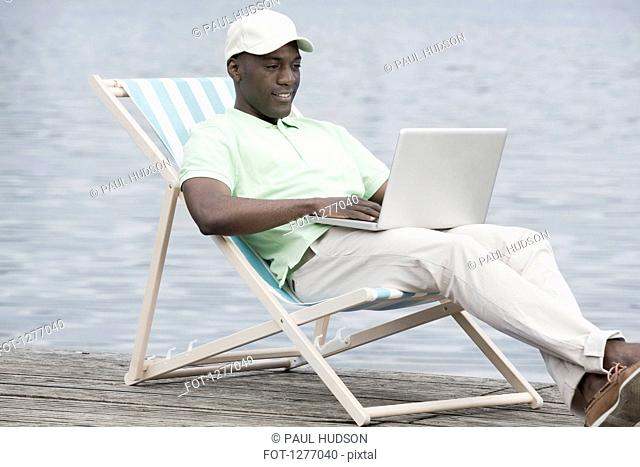 Man relaxing on deck chair using laptop by lake