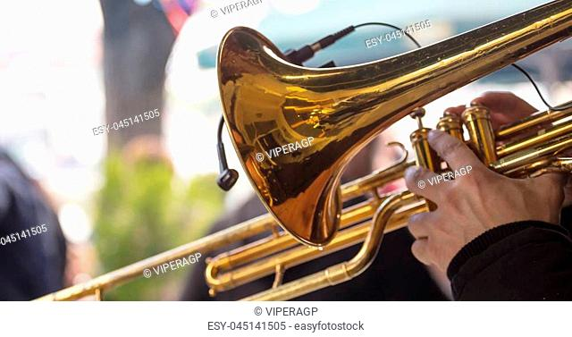 Musician with brass trumpet plays, pressing the valves with his fingers, classical music. Close up view with details, blurred background