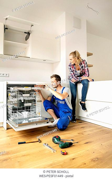 Couple fitting dishwasher in their new built-in kitchen