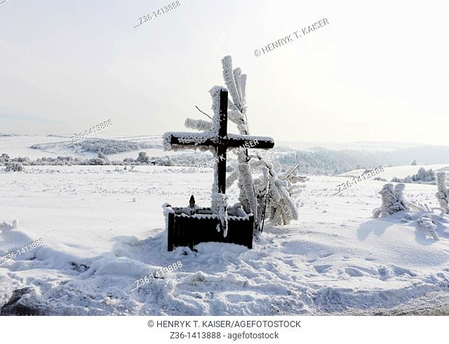 Winter scene, wooden chapel by a road