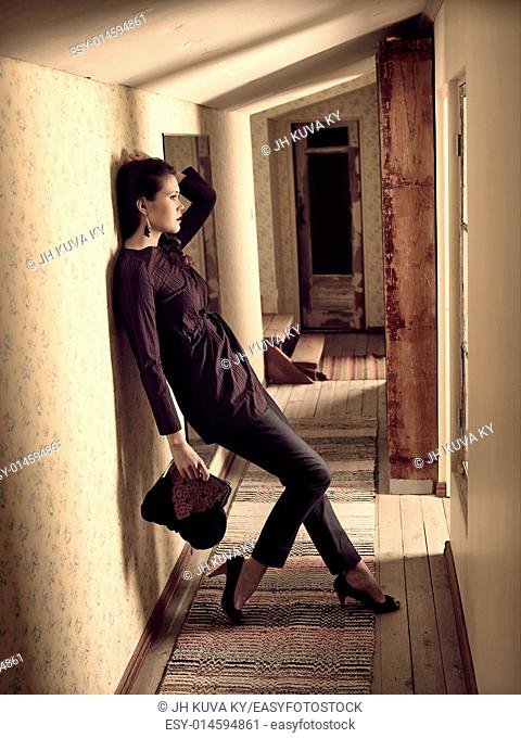 Fashionable girl holds a handbag and she leans on the wall - retro room, cross processed image